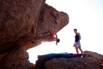 Climber bouldering with a climbing mat underneath him and a friend spotting