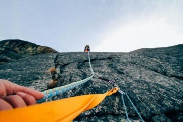 Climber belaying his partner on a rock face