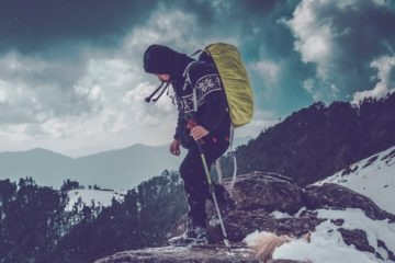 Man mountaineering with his equipment on a snow-covered mountain
