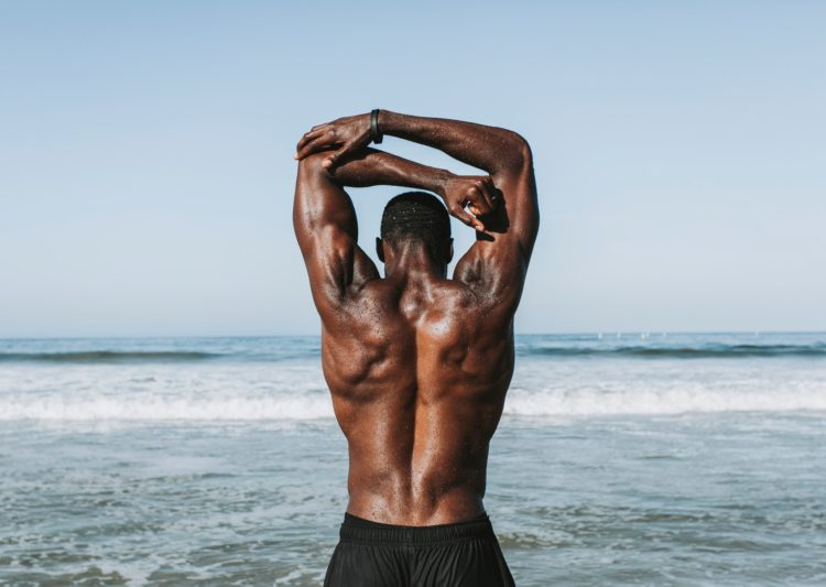Athletic man stretching to avoid a hunchback