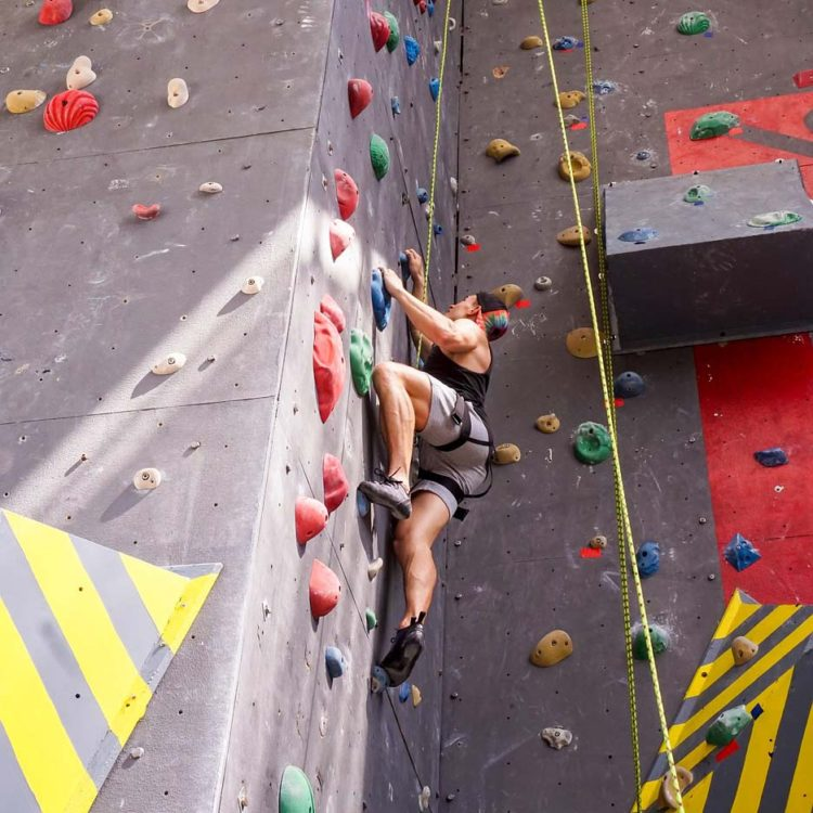 Man climbing indoor (bouldering) wondering how high the climbing wall is