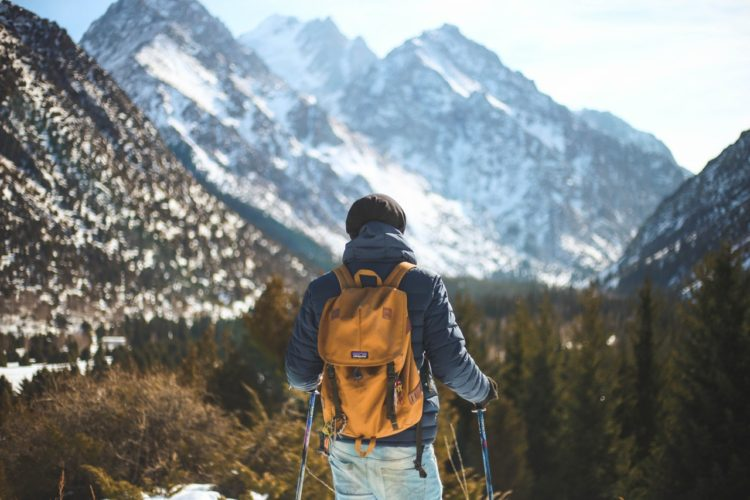Man hiking on a mountain with a backpack and hiking sticks