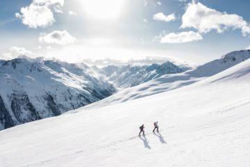 Two men climbing a snow-covered mountain