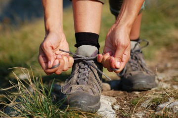 Woman lacing up her hiking boots which are one size bigger
