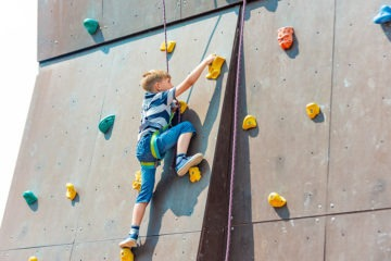 Young 7-year-old kid climbing up a bouldering wall